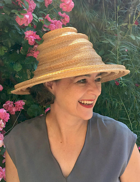 Milliner Nicki Marquardt München wears a collapsible couture straw hat